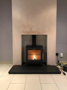 A Boxed & Lipped Honed Granite Hearth into an open fireplace
