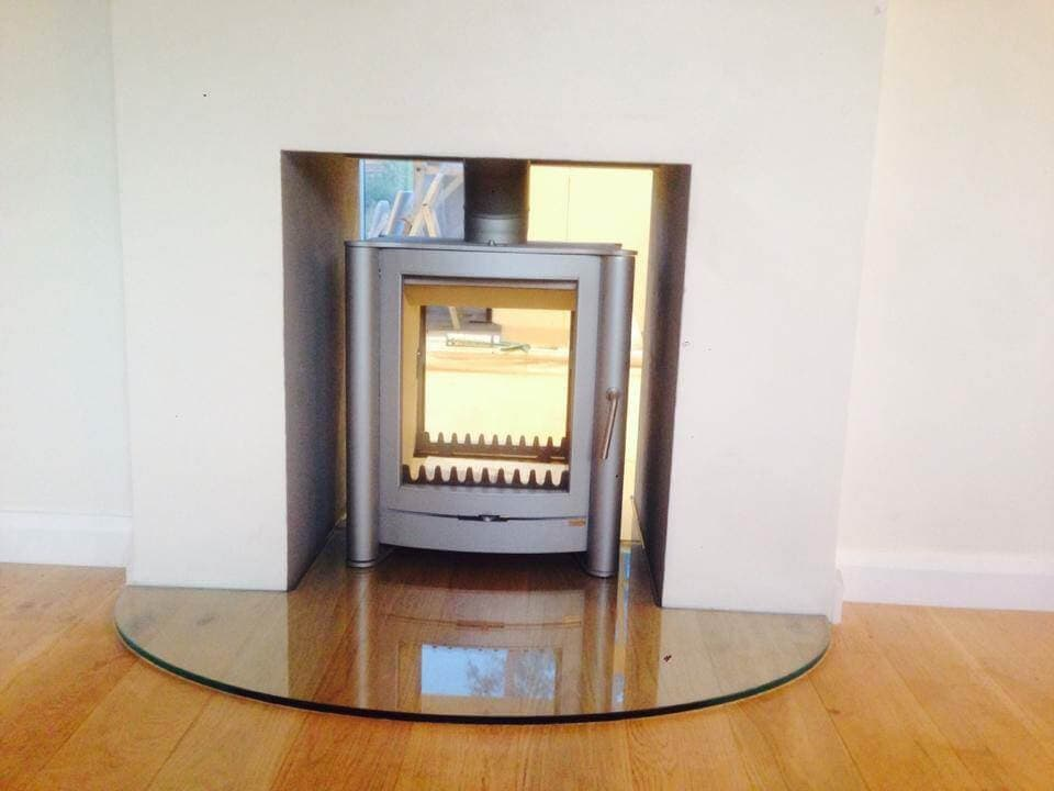 A clear semi-circular 12mm Hearth for a double-sided stove